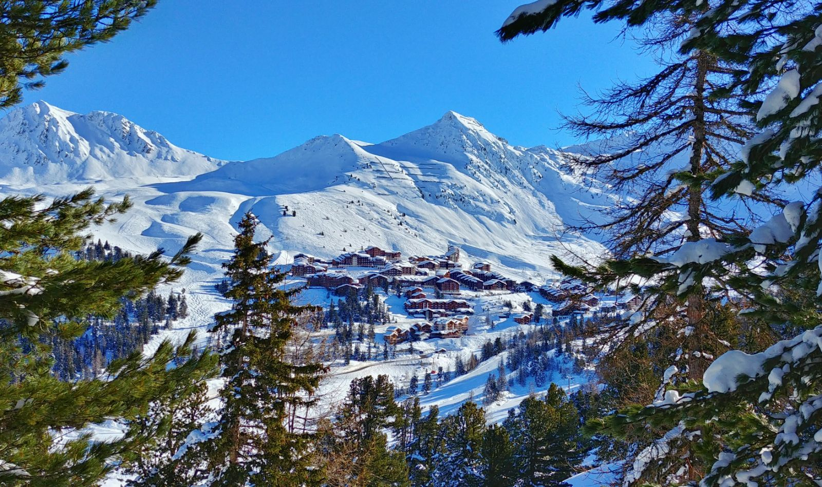 View on snowy French Alps and wooden chalets