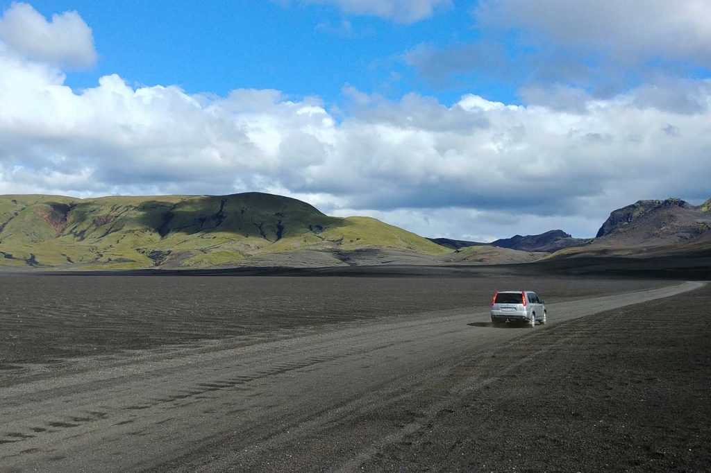 Car passing through an empty road in Iceland