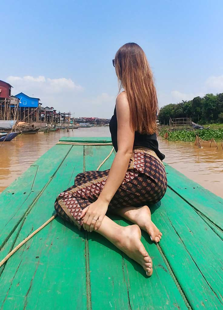 Sitting on a front deck of the green boat overlooking the Tonle Sap lake where the colorful houses are built on stilts