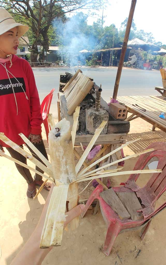 Khmer woman standing outside near the road next to the bamboo sticks with rice inside that are cooked on the stove