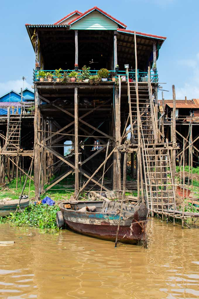 House on stilts with a high ladder and a boat docked on the riverside beneath the house