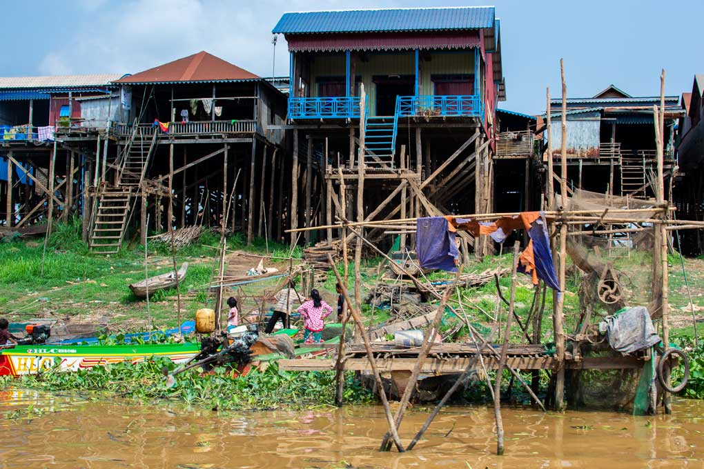 Cambodian people working by the river beneath the house on stilts