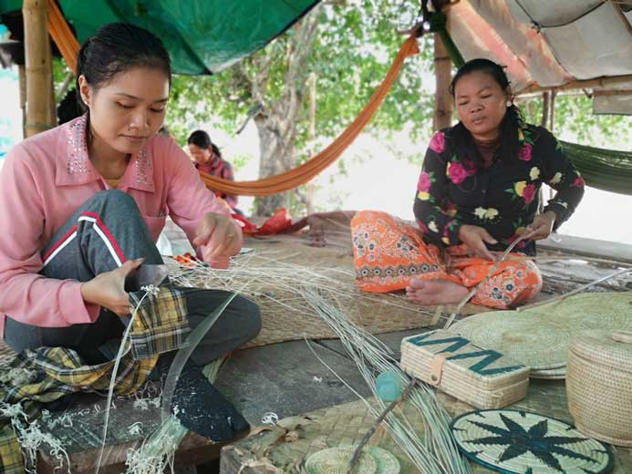 Cambodian women doing hand work with tools and rattan