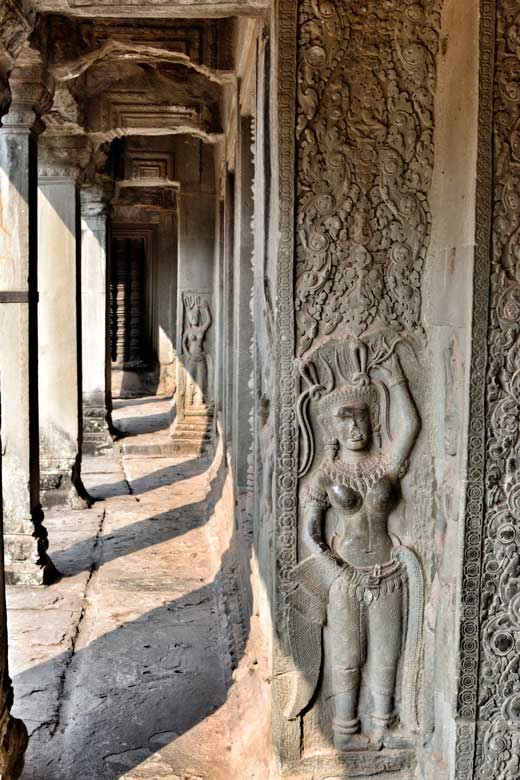 Apsara carvings in the wall showing mythological nymphs
