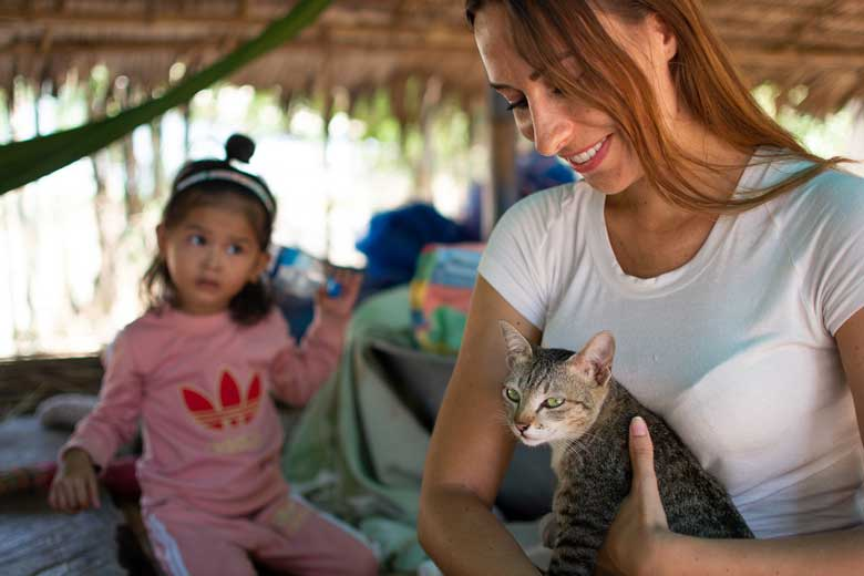 Holding a cat with Cambodian girl watching