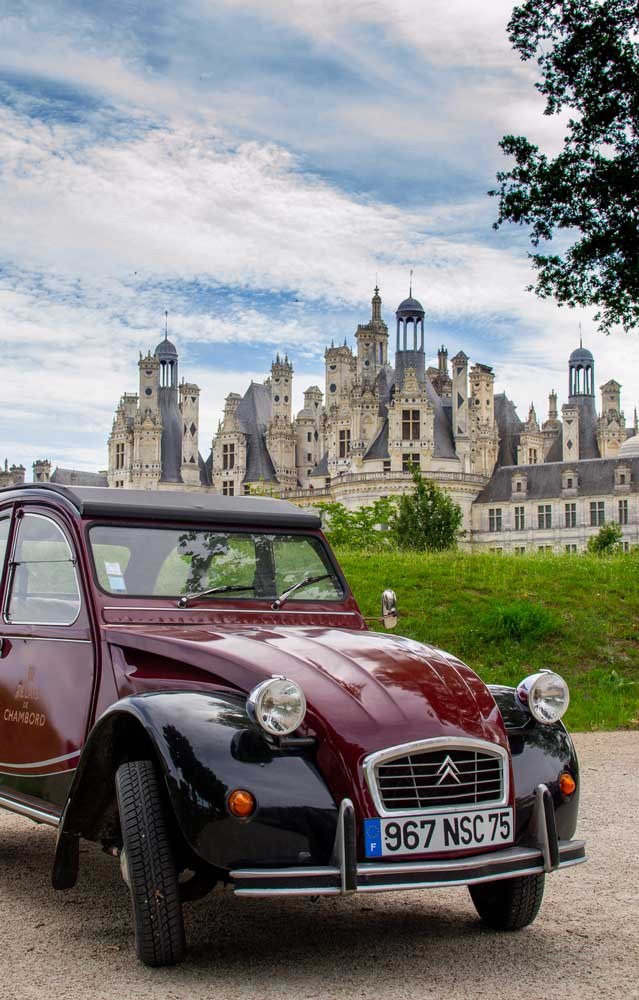 A vintage car with Chambord Castle in the background