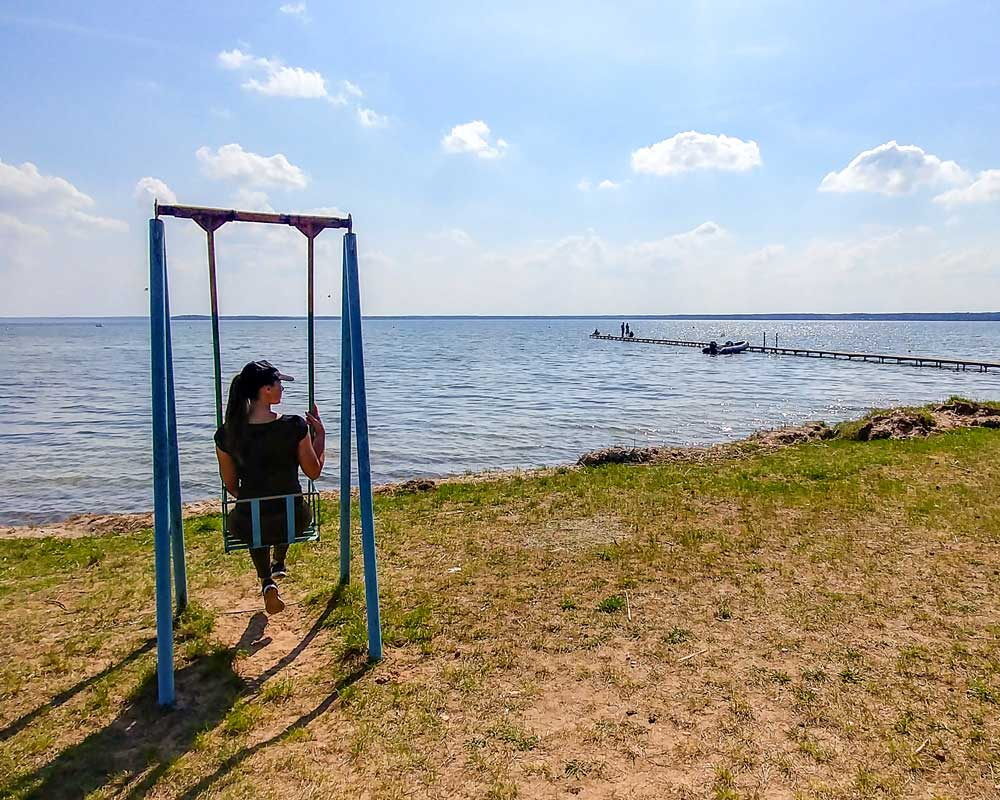 Sitting on a swing by the lake Narach in Belarus